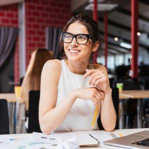 Female bookkeeper sitting at desk smiling.